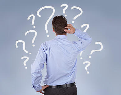 Image description: Man in blue shirt against blue background. He is scratching the back of his head/neck and is depicted surrounded by numerous white question marks.