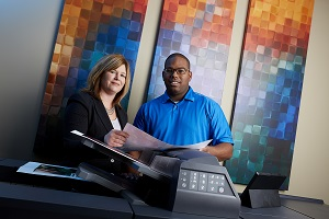 Two employees standing by a multi-function printer reviewing a document together