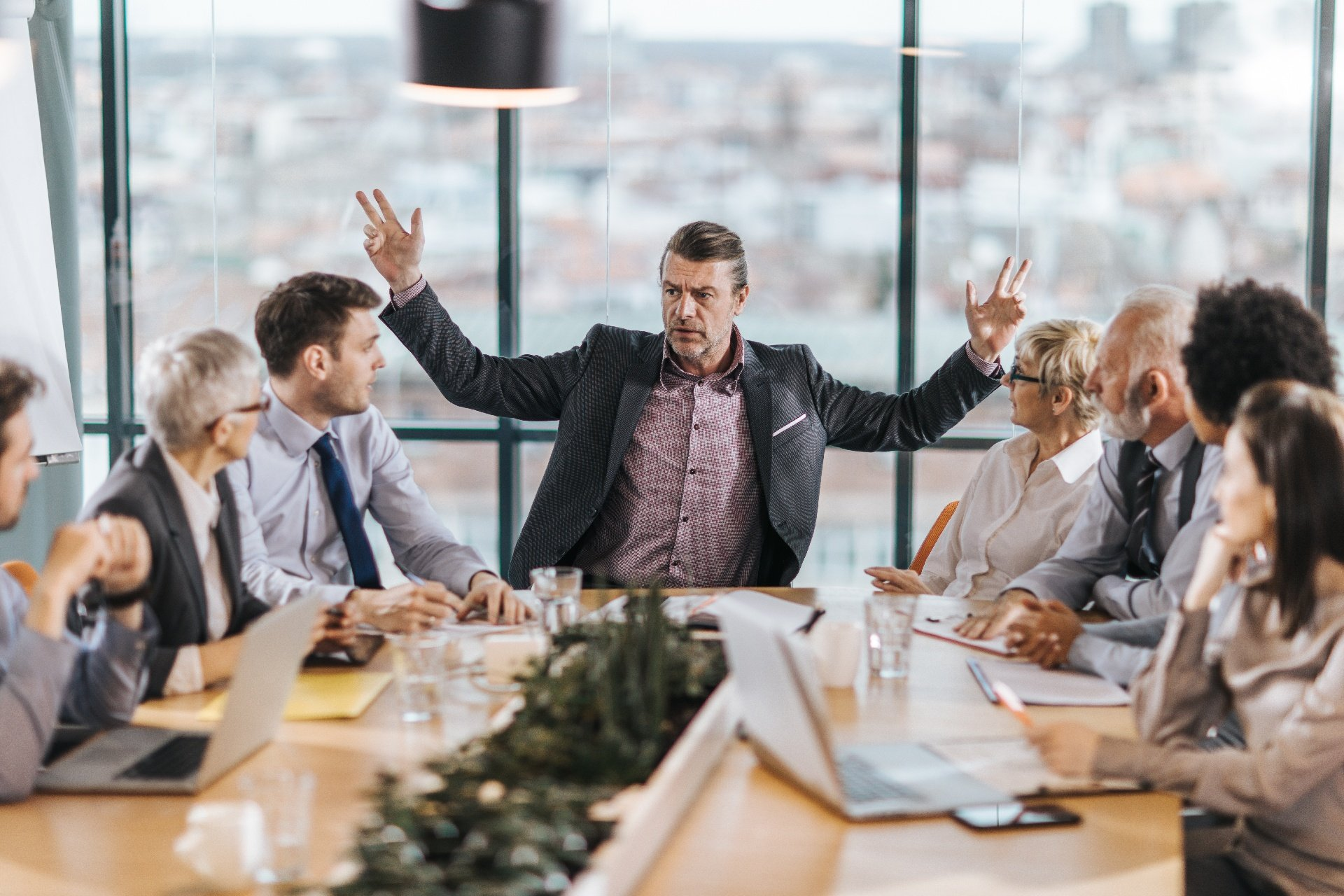 Man at in conference room gesturing angrily