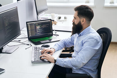man sitting at his desk looking at code on his computer