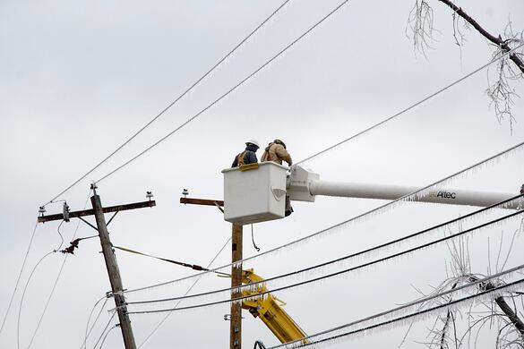 Electrical workers up in a bucket working on power lines