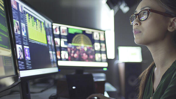 Image of an adult IT worker assessing data profiles on three monitors.