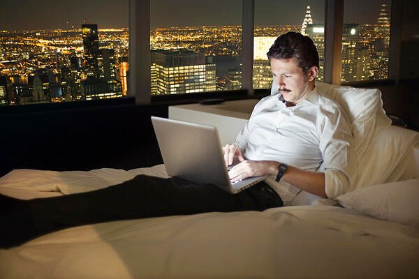 Employee working remotely in a hotel room with a laptop at night.