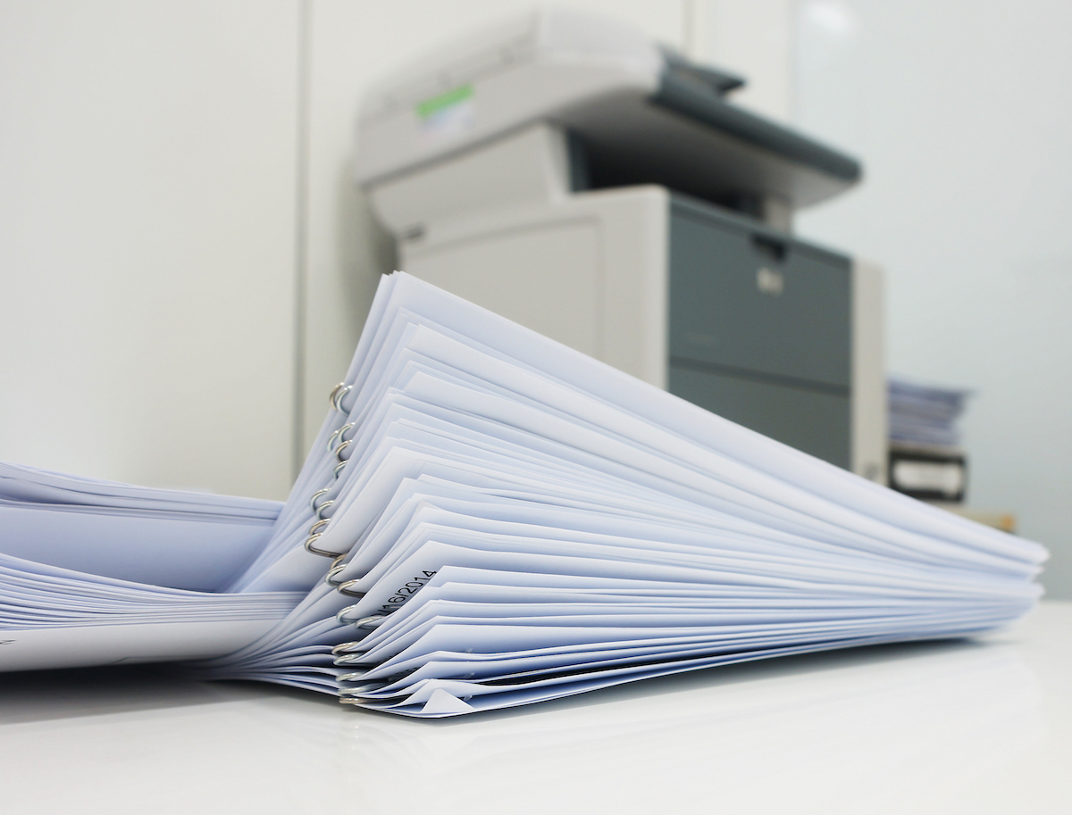 Stack of paper clipped documents with a multi-function printer in the foreground.