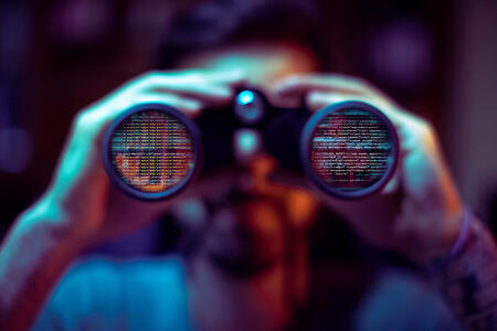Cybercriminal using binoculars to read private company data