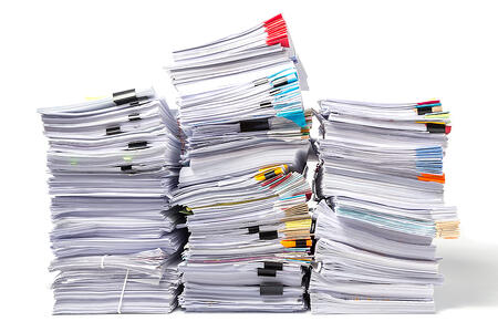 Image of three stacks of business documents with various colors of clips and tabs.