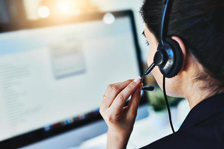 A help desk support staff member with a headset on looking at a computer screen
