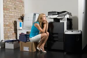 Image description: Woman crouching on a box in front of a non-working computer with head cradled in hands and an annoyed/frustrated upward expression.