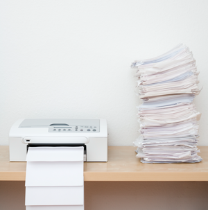 printer on desk with stack of paper