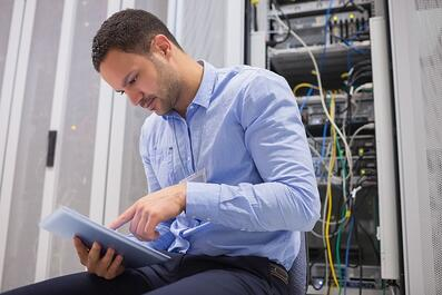 Man looking at a document while working on a server system
