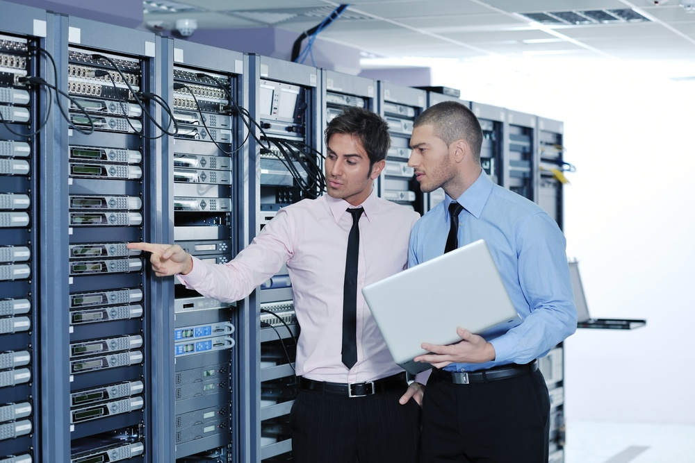 two men discussing IT resources while inspecting a bank of computer equipment