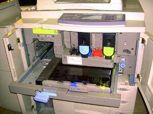 Image of a multi-function printer where the toner compartment is open and you can view the machine's interior.