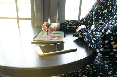 Business owner using a tablet to assess user data.