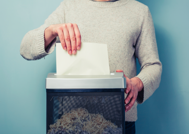 Image of a person's torso standing behind a document shredder. The person is shredding a document.