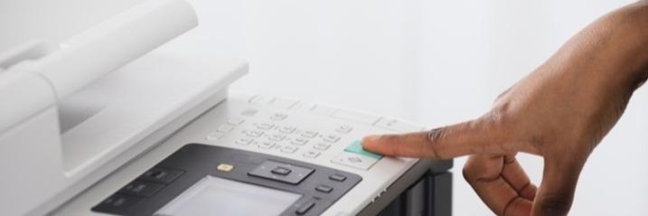 someone pressing print on a multi-function printer