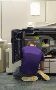 Image description: Male wearing purple shirt kneeling in front of a multifunction printer with the interior components exposed.