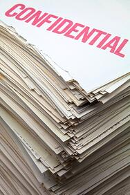 Stack of papers with the word confidential stamped on top of them.