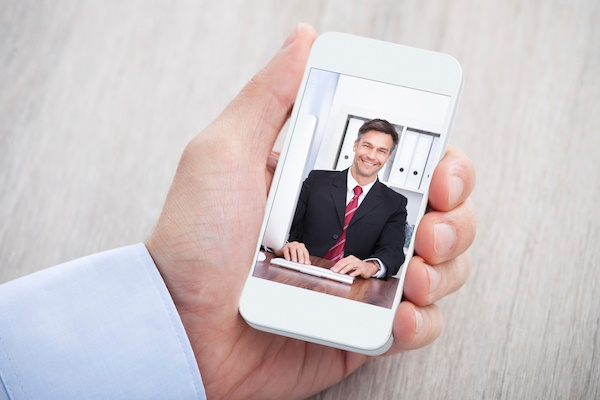 Image description: hand holding a smartphone depicting a mobile conference call with a businessman in a black blazer and red tie.