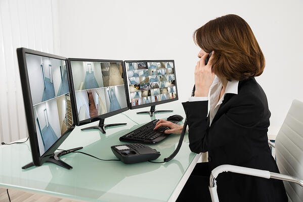 remote video surveillance being monitored by employee with shoulder length hair