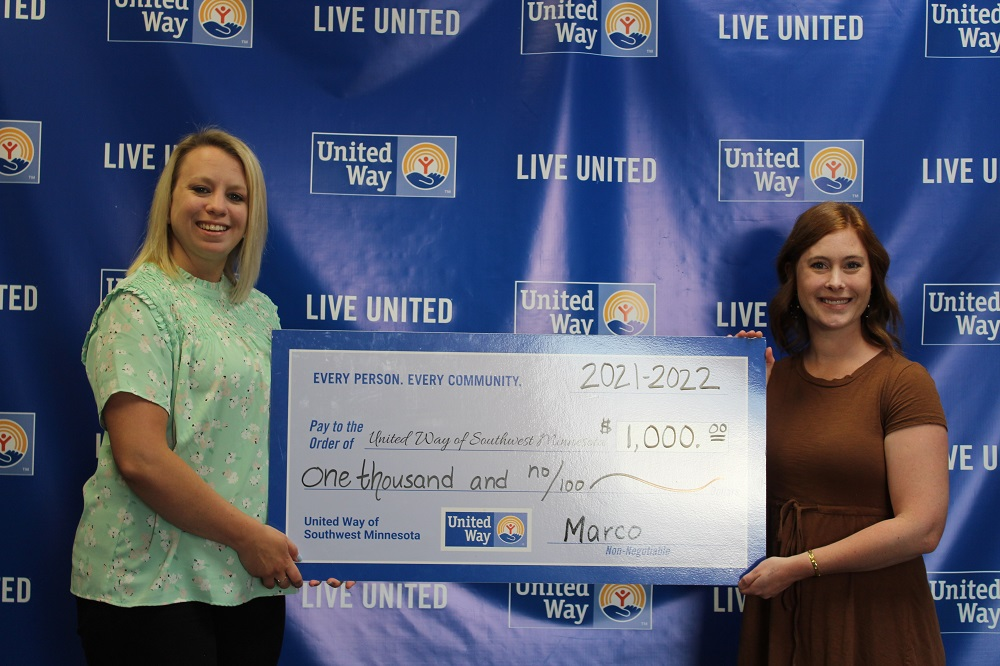 Erin VanderVeen, right, a Marco technology advisor, presents a $1,000 donation to Sarah Kicmal, chief executive officer and president of United Way of Southwest Minnesota.
