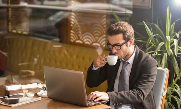 business man at a laptop sipping coffee